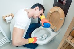 De mens is een weerzinwekkend beetje het schoonmaken van het toilet royalty-vrije stock fotografie