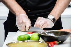 De mens in een zwarte eenvormige chef-kok sneed groenten op de lijstclose-up Royalty-vrije Stock Fotografie