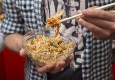 De mens eet gebraden rijst met eetstokjes voor sushi Royalty-vrije Stock Fotografie