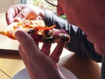 De mens eet plak van pizza Royalty-vrije Stock Afbeelding