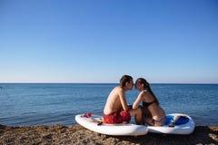 De mens en het jonge sexy meisje kussen bij sup surfen bij de oceaan in zonneschijn Conceptenlevensstijl, sport, liefde Royalty-vrije Stock Afbeeldingen
