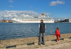 De mens en het meisje kijken op Klaipeda-haven en internationaal cruiseschip op Curonian-Lagune, Klaipeda Litouwen royalty-vrije stock afbeelding