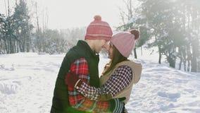 De mens en het meisje koppelen wat betreft hun hoofden in de winterpark, zonnige dagsneeuw, langzame mo stock videobeelden