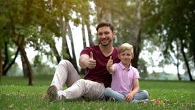De mens en de jongen tonen duimen, sociale steun voor alleenstaande ouderfamilie, welzijn royalty-vrije stock foto's