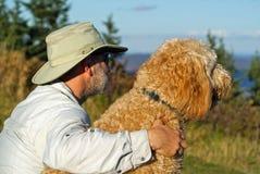 De mens en Zijn Hond genieten van een Toneelmening Stock Foto's