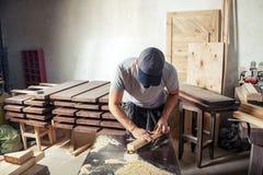 De mens evenaart houten met een malenmachine Royalty-vrije Stock Afbeeldingen