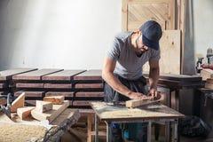 De mens evenaart houten met een malenmachine stock foto's