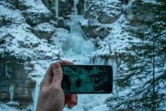 De mens fotografeert de bevroren waterval in Kuhflucht Royalty-vrije Stock Foto's