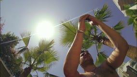 De mens fotografeert op telefoon een panorama onder palmen stock video