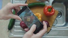 De mens fotografeert verse groenten bij scherpe raad stock footage