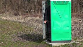 De mens gaat aan in groen draagbaar toilet stock videobeelden