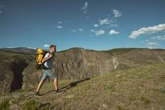 De mens gaat bergop met een rugzak op zijn rug stock fotografie