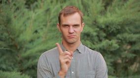 De mens gaat niet akkoord Hij neigt zijn hoofd in ontkenning het golven van zijn vinger stock video