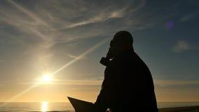De mens in gasmasker bij kust las een boek langzaam motiesilhouet stock video