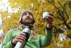 De mens in gebreide hoed en sjaal, met glimlach biedt een hete drank - thee of koffie van thermosflessen aan iemand, bodemmening  stock foto's