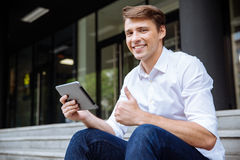 De mens gebruikend tablet en tonend beduimelt omhoog in openlucht stock foto's