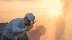 De mens gebruikt een doek om zonnepanelen schoon te maken, omhoog sluit stock footage