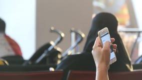 De mens gebruikt een smartphone in luchthaven het wachten zitkamer Verwachtingen van vlucht bij luchthaven stock video
