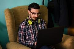 De mens gebruikt laptop op bank in zijn huis royalty-vrije stock foto