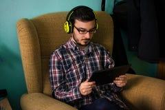 De mens gebruikt tablet op bank in zijn huis royalty-vrije stock afbeeldingen