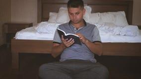 De mens gebruikt de te lezen boeken van een handtik Sluit omhoog van open boek met pagina's het wegknippen Pagina van Bijbel stock videobeelden