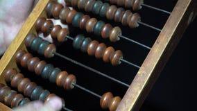 De mens gebruikt uitstekend oud telraam Mannelijke hand op uitstekend houten rekeningenclose-up stock video