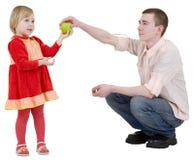 De mens geeft appel aan het meisje Stock Foto