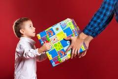 De mens geeft een gift aan kleinzoon op een rode achtergrond royalty-vrije stock foto's