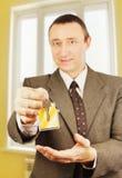 De mens geeft sleutels met keychain in de vorm van een klein huis in een flat Royalty-vrije Stock Fotografie