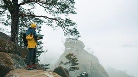 De mens in geel jasje beklimt de rotsen in de de winterbergen stock video