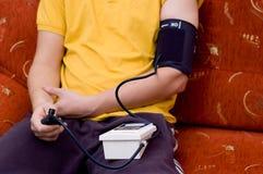 De mens in geel overhemd controleert bloeddruk Stock Foto's