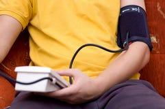 De mens in geel overhemd controleert zijn bloeddruk Stock Foto