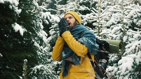 De mens in geel de winterjasje maakt zijn handen van sneeuw schoon die zich in het bergbos bevinden stock video