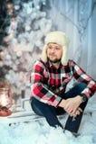 De mens gekleed in een plaidoverhemd, jeans en een bonthoed zit op een achtergrond van Kerstmislichten en een Kerstboom op de ach Stock Afbeelding
