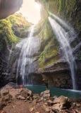 De mens is gelukkig op rotsen in Madakaripura-waterval in tropisch regenwoud stock foto's
