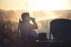 De mens geniet van drinkend koffie in openlucht zittend als voorzitter tijdens nevelige ochtendzonsopgang op het kamperen plaats  royalty-vrije stock foto's