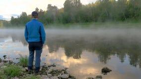 De mens geniet van duidelijk meer met ochtend mist en het wijzen van op hemel stock video