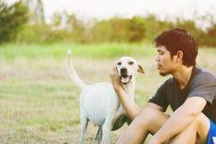 De mens geniet van in weide met huisdier stock foto