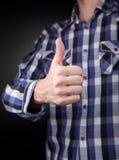 De mens in geruit overhemd met duimen ondertekent omhoog Royalty-vrije Stock Foto