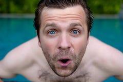 De mens is geschokt met nieuws Hij sluit zijn mond Hij zwemt in pool tijdens vakantie Royalty-vrije Stock Foto's