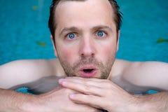 De mens is geschokt met nieuws Hij sluit zijn mond Hij zwemt in pool tijdens vakantie Royalty-vrije Stock Afbeelding