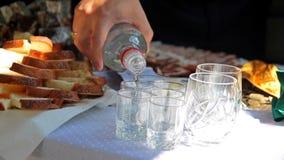 De mens giet wodka in wijnglazen afkoop van de bruid De traditie van het huwelijk stock footage