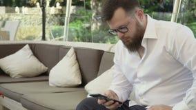 De mens in glazengebruik telefoneert en ontspant in in openlucht restaurant stock videobeelden