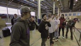 De mens in GLB spreekt in microfoon aan mensen in skatepark Rolschaatsers competition Gastheercameraman stock footage