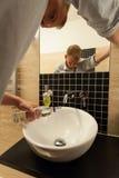 De mens goot een fles wodka onderaan de gootsteen Royalty-vrije Stock Foto's
