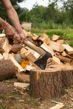 De mens hakt hout met bijl Stock Foto's