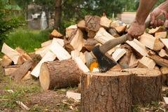 De mens hakt hout met bijl Stock Foto