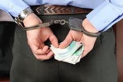 De mens in handcuffs houdt geld in zijn palmen achter zijn rug Royalty-vrije Stock Afbeelding