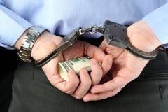 De mens in handcuffs houdt geld in zijn palmen achter zijn rug Royalty-vrije Stock Afbeeldingen