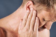 De mens heeft een pijnlijk oor Mens die aan hoofdpijn op blauwe achtergrond lijden royalty-vrije stock foto